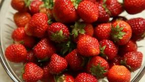 Frische strawberriers in der Glasschüssel auf beige Hintergrund stock footage