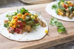 Frische Tacos mit Huhn, Gemüse und Kräutern auf einem hölzernen Brett Stockbild