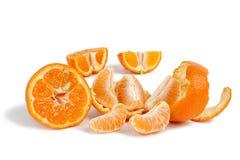 Frische Tangerinescheiben und -keile auf einem weißen Hintergrund stockbilder