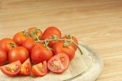 Frische Tomaten auf dem Küchentisch Tomaten auf einem hölzernen Schneidebrett Inländische Bearbeitung des Gemüses Lizenzfreies Stockbild