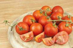 Frische Tomaten auf dem Küchentisch Tomaten auf einem hölzernen Schneidebrett Inländische Bearbeitung des Gemüses Stockfotos