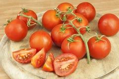 Frische Tomaten auf dem Küchentisch Tomaten auf einem hölzernen Schneidebrett Inländische Bearbeitung des Gemüses Stockfotografie