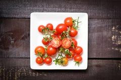 Frische Tomaten auf weißer Platte mit hölzernem dunklem Hintergrund stockfotografie