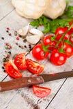 Frische Tomaten, Brötchen, Gewürze und altes Messer Lizenzfreie Stockfotos