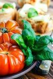 Frische Tomaten mit Basilikum für Gebrauch, wie, Bestandteile mit Kopienraum kochend Tomaten mit Basilikum auf Holztischhintergru Lizenzfreies Stockbild