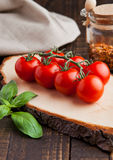 Frische Tomaten mit Basilikum und Gewürze rütteln auf Schmutzbrett Lizenzfreie Stockfotografie