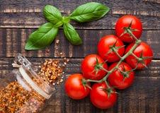 Frische Tomaten mit Basilikum und Gewürze rütteln auf Schmutzbrett Stockfotografie