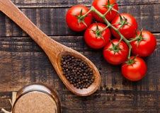 Frische Tomaten mit Basilikum und Löffel mit Pfeffer auf Schmutz verschalen Lizenzfreies Stockbild