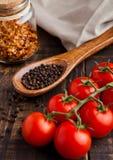 Frische Tomaten mit Basilikum und Löffel mit Pfeffer auf Schmutz verschalen Lizenzfreie Stockbilder