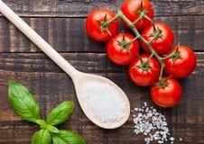Frische Tomaten mit Basilikum und Löffel mit Salz auf Schmutz verschalen Stockbild