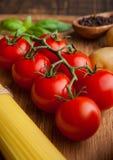 Frische Tomaten mit rohem spagetti und Pfeffer auf Küche verschalen Stockfoto