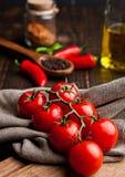 Frische Tomaten mit rotem und schwarzem Pfeffer auf Geschirrtuch Lizenzfreie Stockbilder