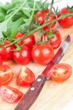 Frische Tomaten, rucola und altes Messer Stockbild
