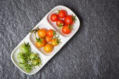Frische Tomatenkirschorganische/grüne und reife rote Tomaten in der Schale mit dunklem Hintergrund lizenzfreie stockbilder