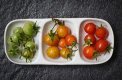 Frische Tomatenkirschorganischer - grüne und reife rote Tomaten in der Schale mit dunklem Hintergrund - selektiver Fokus lizenzfreies stockfoto