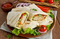 Frische Tortillaverpackungen mit Kebab und Frischgemüse auf Platte Lizenzfreies Stockfoto
