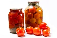 Frische und in Büchsen konservierte rote Tomaten auf weißem Hintergrund Lizenzfreie Stockfotos