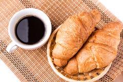 Frische und geschmackvolle französische Hörnchen in einem Korb und in einem Tasse Kaffee dienten Lizenzfreies Stockfoto