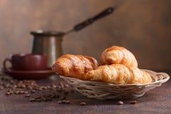 Frische und geschmackvolle Hörnchen und Tasse Kaffee auf alter Kupferrückseite lizenzfreies stockfoto