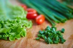 Frische und geschmackvolle Tomaten, Salat, Zwiebel auf Schneidebrett Lizenzfreies Stockbild