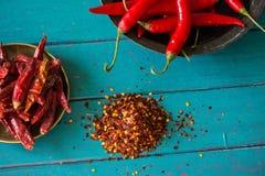 Frische und getrocknete heiße Paprikas in der Schüssel und in den Samen auf Tabelle Stockfotos