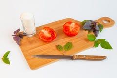Frische und reife Tomaten, Basilikum, Salz und Messer auf Schneidebrett Stockbild