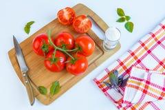 Frische und reife Tomaten, Basilikum, Salz und Messer auf Schneidebrett Lizenzfreies Stockbild