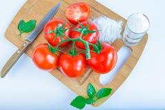 Frische und reife Tomaten, Basilikum, Salz und Messer auf Schneidebrett Stockfotos