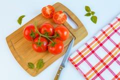 Frische und reife Tomaten, Basilikum und Messer auf Schneidebrett Stockfoto