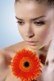 Frische und schöne junge Frau mit gerber Blume Stockfotos