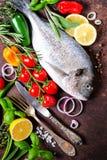 Frische ungekochte Fische, dorado, Seebrassen mit Zitrone, Kräuter, Gemüse und Gewürze auf rustikalem Hintergrund Beschneidungspf Lizenzfreie Stockbilder