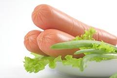 Frische Würste auf einer Platte mit Gemüse. Stockbild