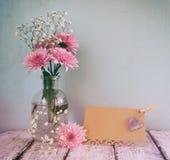 Frische weiße und rosa Blumen, Herz nahe bei leerer Karte der Weinlese über Holztisch gefiltertes und getontes Bild der Weinlese Lizenzfreies Stockbild