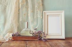 Frische Weinleseparfümflasche nahe bei aromatischen Blumen und antiker leerer Rahmen auf Holztisch Retro- gefiltertes Bild Stockfoto