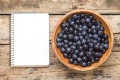 Frische wilde Beeren mit leerem Rezept buchen auf hölzernem Hintergrund Stockfotos