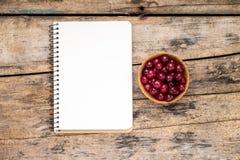 Frische wilde Beeren mit Papiernotizbuch auf Holztisch Stockbild