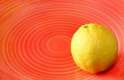 Frische Zitrone auf roter Platte mit gewundenem Muster Stockbilder