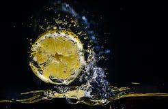 Frische Zitrone, die im Wasser über Schwarzem spritzt Lizenzfreies Stockfoto