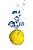 Frische Zitrone fiel in Wasser mit Blasen Stockbilder