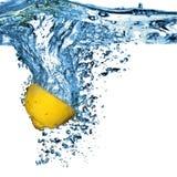 Frische Zitrone fiel in Wasser mit Luftblasen Lizenzfreie Stockfotografie