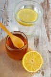 Frische Zitrone mit Honig und Glas Wasser mit Scheibe der Zitrone Stockbild