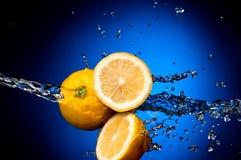 Frische Zitrone in spritzt vom Wasser Lizenzfreie Stockfotos