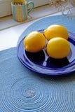 Frische Zitronen auf einem blauen Plattenporträt weit Stockbild