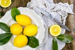 Frische Zitronen auf rustikaler weißer Platte Lizenzfreie Stockfotos