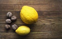 Frische Zitronen und Nüsse auf dem hölzernen backround, Bestandteile, fres stockfotos