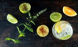 Frische Zitronen und Zitronen-Wasser auf Holztisch Lizenzfreie Stockbilder