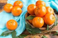 Frische Zitrusfruchttangerinen, Orangennahaufnahme in der rustikalen Art Stockfotos