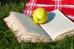 Frischer Apfel und offenes Buch Lizenzfreie Stockfotografie