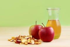 Frischer Apfelsaft, rote Äpfel und getrocknete Äpfel auf hölzernem Hintergrund Lizenzfreie Stockfotos