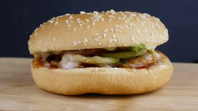 Frischer appetitanregender Hamburger besprühen die Samen des indischen Sesams, die auf schwarzen Hintergrund sich drehen stock video
